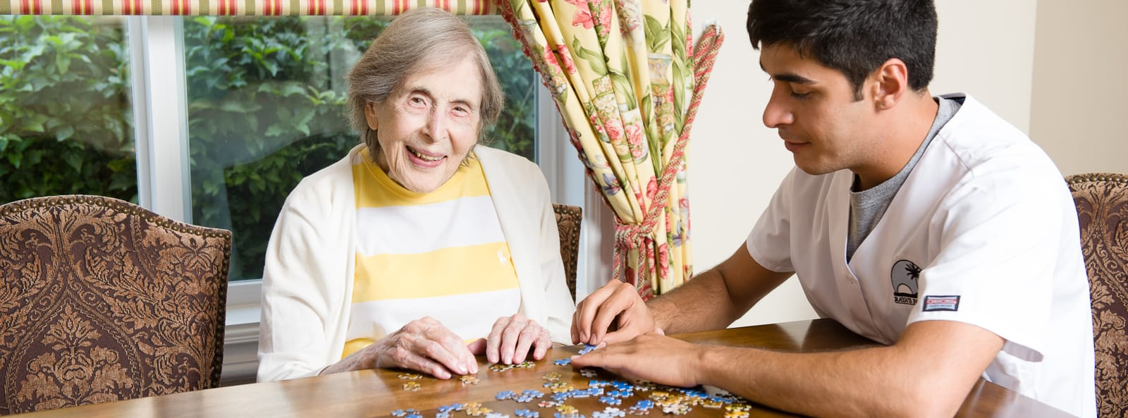 woman doing puzzle with staff member