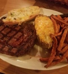 Jaspers Smokehouse & Steaks - Big Bear Lake, CA. delicious ribeye with twice baked potato, cheesy bread and sweet potato fries